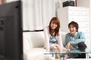 テレビを見て笑うカップル